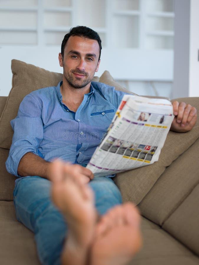 Νεαρός άνδρας που χαλαρώνει και που ονειρεύεται στον καναπέ στο σπίτι στοκ φωτογραφίες