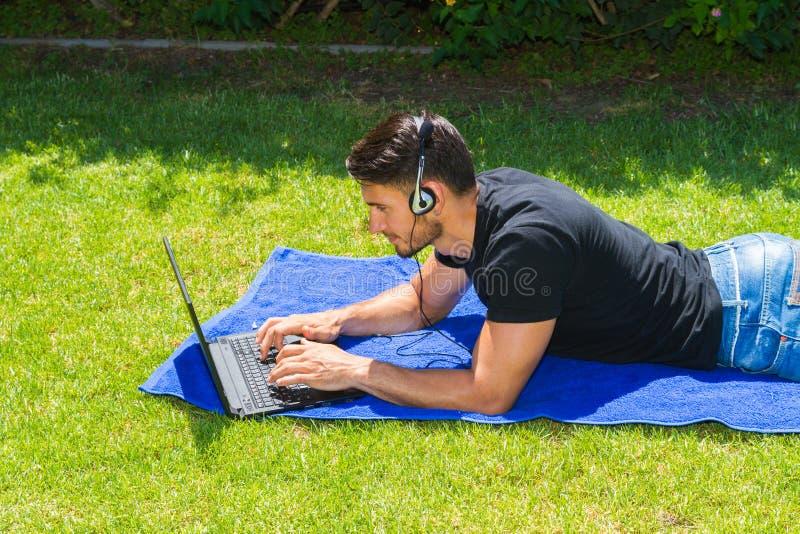 Νεαρός άνδρας που χρησιμοποιεί ένα lap-top και τα ακουστικά υπαίθρια στοκ φωτογραφίες με δικαίωμα ελεύθερης χρήσης