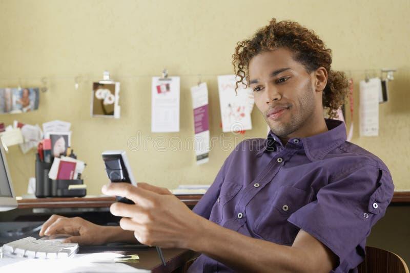 Νεαρός άνδρας που χρησιμοποιεί το κινητό τηλέφωνο στην αρχή στοκ φωτογραφία