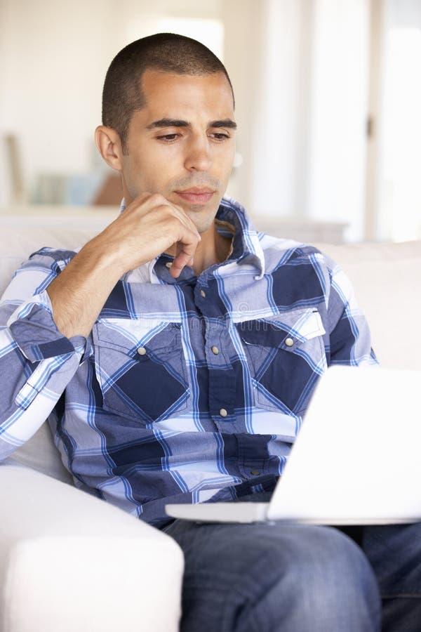 Νεαρός άνδρας που χρησιμοποιεί το φορητό προσωπικό υπολογιστή στο σπίτι στοκ φωτογραφίες