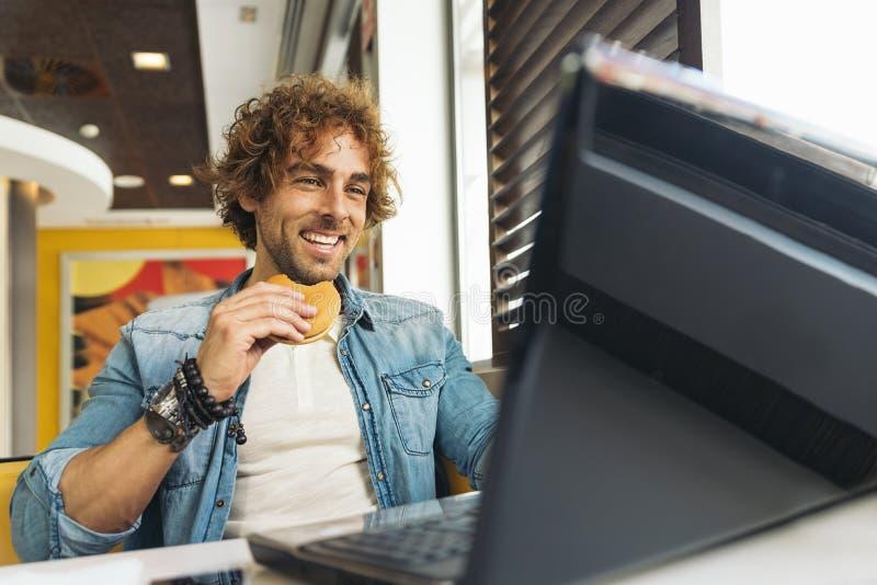 Νεαρός άνδρας που χρησιμοποιεί το lap-top ενώ για να έχει το μεσημεριανό γεύμα στοκ φωτογραφία