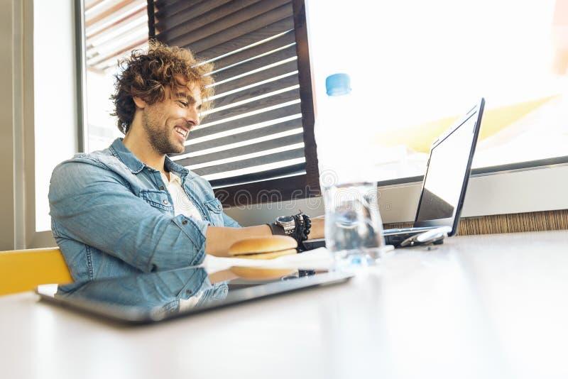 Νεαρός άνδρας που χρησιμοποιεί το lap-top ενώ για να έχει το μεσημεριανό γεύμα στοκ εικόνα με δικαίωμα ελεύθερης χρήσης