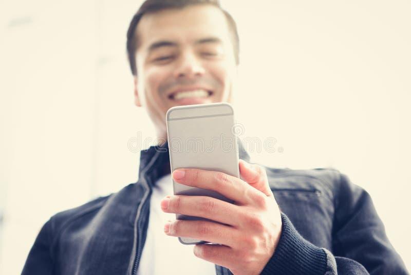 Νεαρός άνδρας που χρησιμοποιεί το smarthone στοκ εικόνα