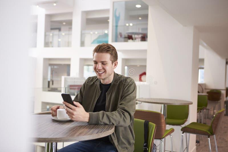 Νεαρός άνδρας που χρησιμοποιεί το smartphone του σε έναν σύγχρονο πανεπιστημιακό καφέ στοκ εικόνα με δικαίωμα ελεύθερης χρήσης
