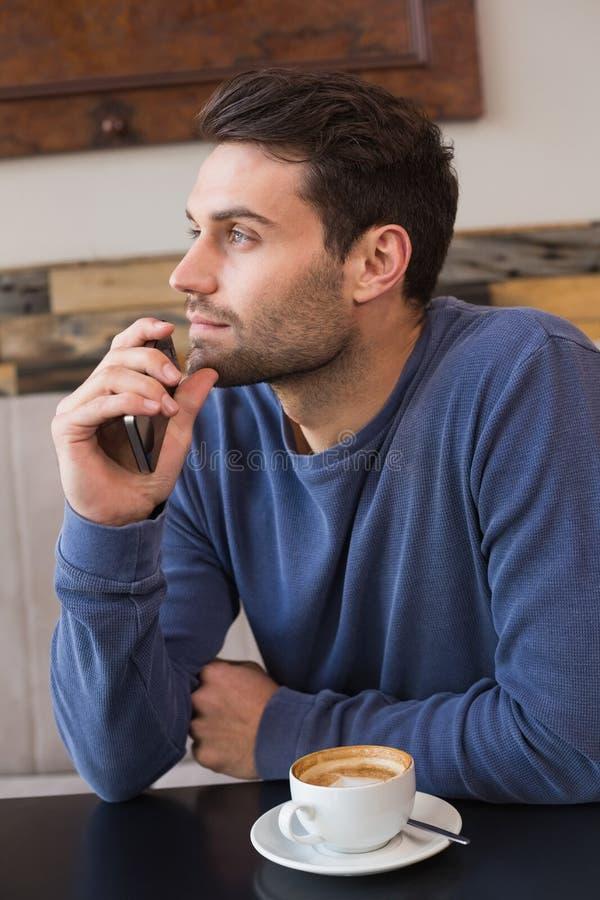 Νεαρός άνδρας που χρησιμοποιεί το smartphone του στοκ εικόνα