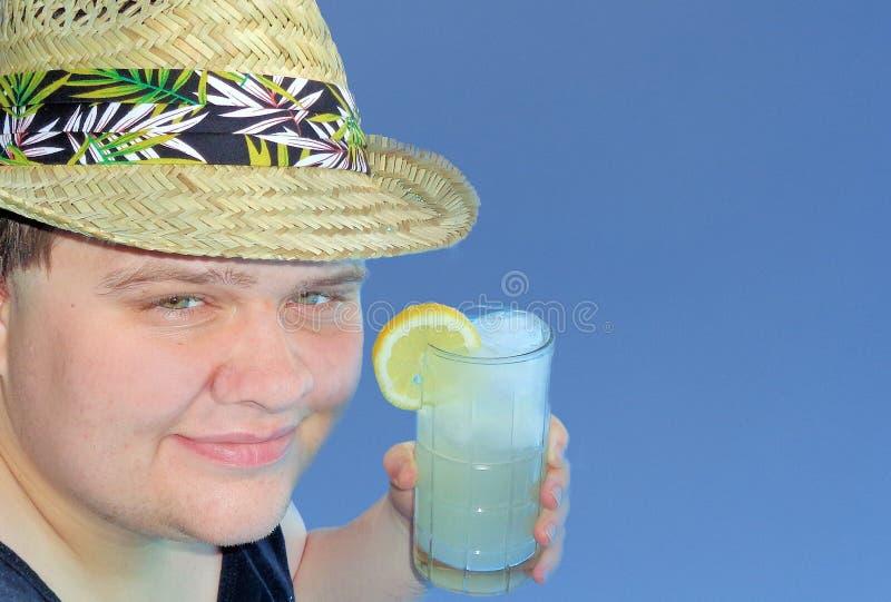 Νεαρός άνδρας σε ένα άχυρο Fedora που κρατά ένα ποτήρι της λεμονάδας στοκ φωτογραφία