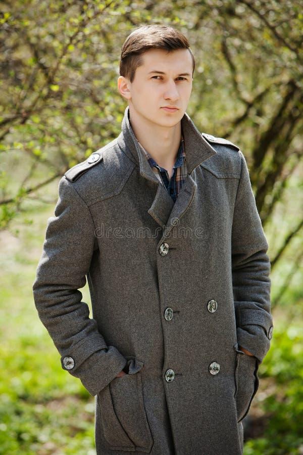 Νεαρός άνδρας σε ένα γκρίζο παλτό στοκ εικόνες