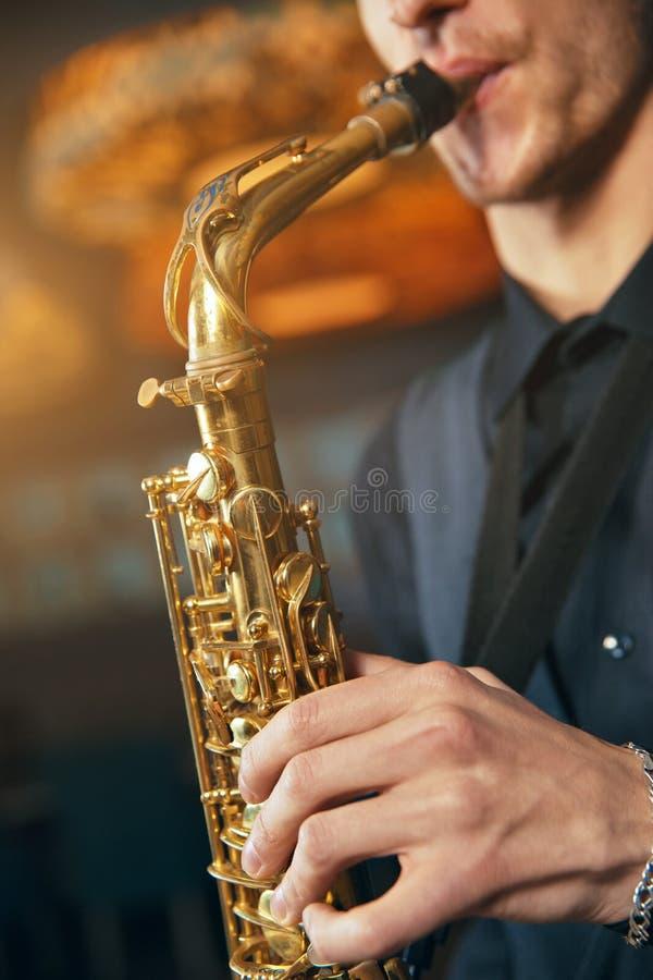 Νεαρός άνδρας σε ένα saxophone λαβής κοστουμιών στοκ φωτογραφία