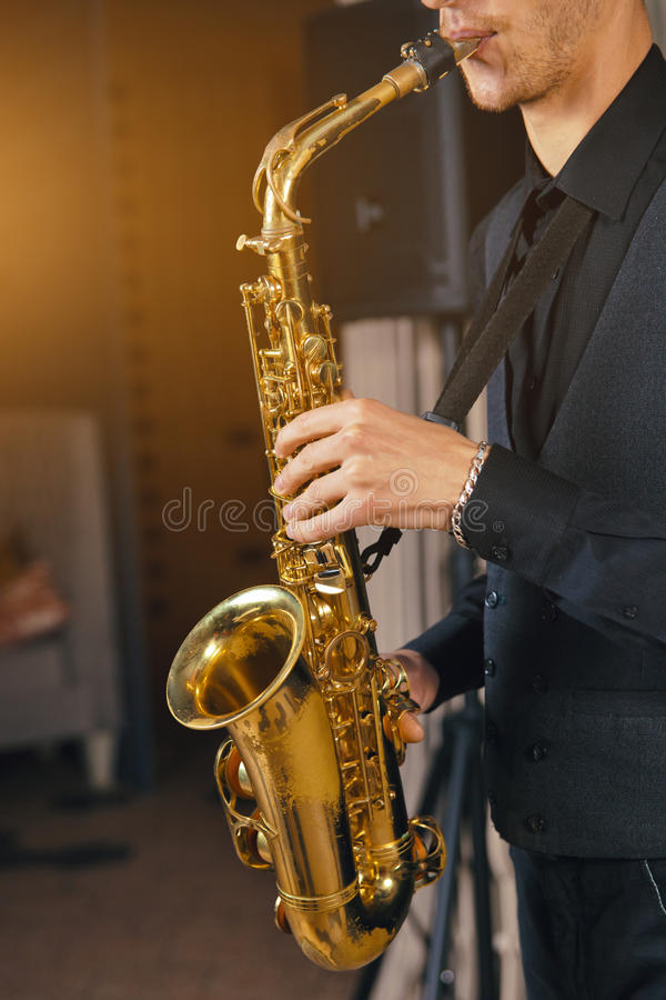 Νεαρός άνδρας σε ένα saxophone λαβής κοστουμιών στοκ εικόνες