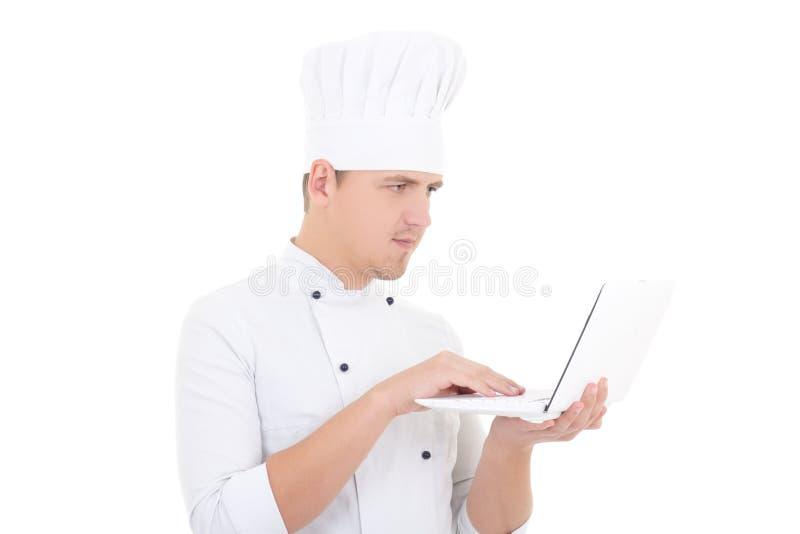 Νεαρός άνδρας σε ομοιόμορφο αρχιμαγείρων με το lap-top που απομονώνεται στο λευκό στοκ φωτογραφία με δικαίωμα ελεύθερης χρήσης