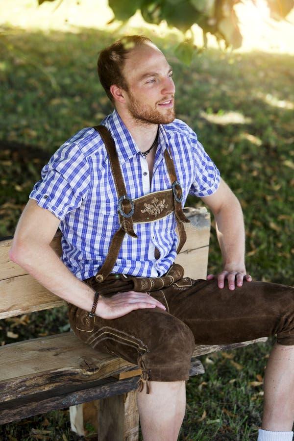 Νεαρός άνδρας στα παραδοσιακά βαυαρικά ενδύματα που κάθεται στον πάγκο στοκ φωτογραφίες