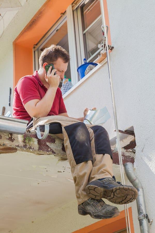 Νεαρός άνδρας στην αποκατάσταση μπαλκονιών στοκ φωτογραφία με δικαίωμα ελεύθερης χρήσης