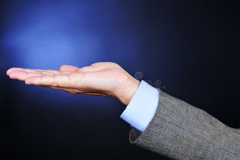 Νεαρός άνδρας στο κοστούμι με το χέρι του ανοικτό στοκ φωτογραφία