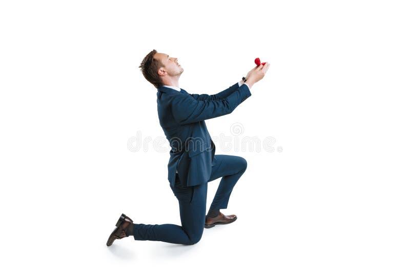 Νεαρός άνδρας στο κοστούμι που στέκεται σε ένα γόνατο και που κάνει την πρόταση γάμου στοκ εικόνα με δικαίωμα ελεύθερης χρήσης