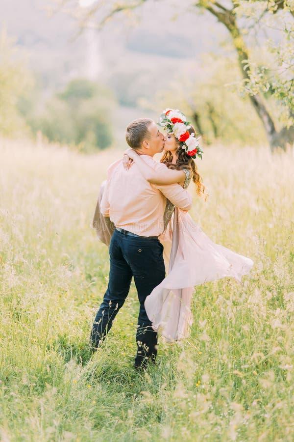 Νεαρός άνδρας στο πουκάμισο ροδάκινων που ανυψώνει επάνω την καλή φίλη του που φορά το ιώδη φόρεμα και το στεφάνι στοκ φωτογραφία με δικαίωμα ελεύθερης χρήσης
