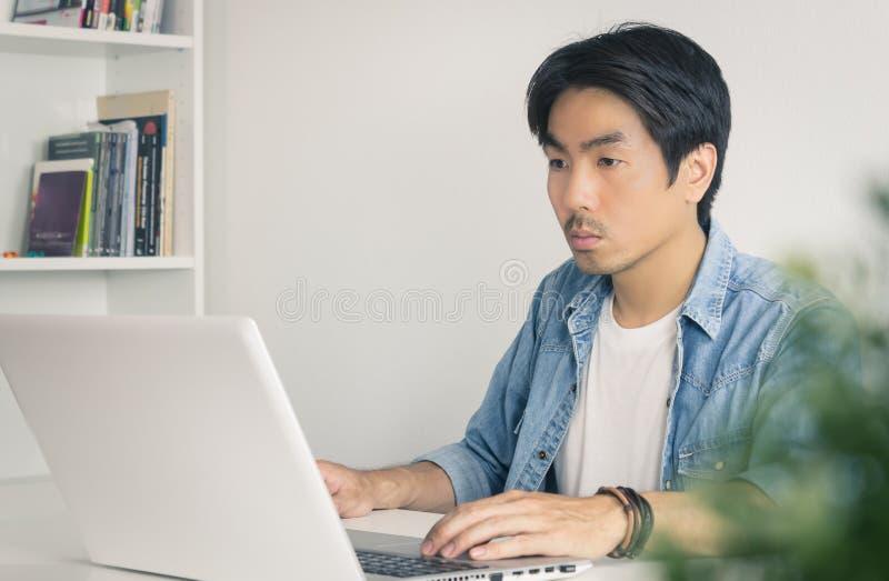 Νεαρός ασιάτης απλός επιχειρηματίας που εργάζεται με φορητό υπολογιστή στο οικιακό γραφείο σε τόνο στοκ εικόνες με δικαίωμα ελεύθερης χρήσης