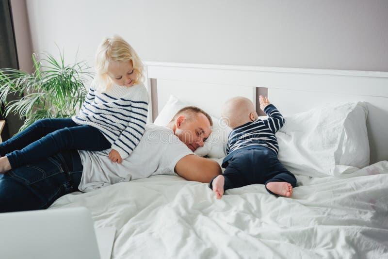 Νεαρός ευτυχισμένος πατέρας ξαπλωμένος στο κρεβάτι ενώ η κόρη του παίζει μαζί του στοκ φωτογραφίες με δικαίωμα ελεύθερης χρήσης