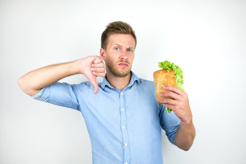 Νεαρός πεινασμένος άνδρας δείχνει πεινασμένος κρατώντας φρέσκο σάντουιτς με φύλλο σαλάτας που δείχνει αντιπάθεια στο λευκό φόντο στοκ φωτογραφία με δικαίωμα ελεύθερης χρήσης