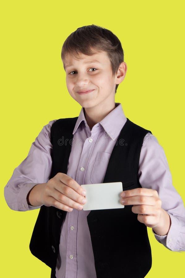 Νεαρός στο επιχειρησιακό κοστούμι που παρουσιάζει άσπρη κενή κάρτα στο κίτρινο υπόβαθρο στοκ φωτογραφία με δικαίωμα ελεύθερης χρήσης