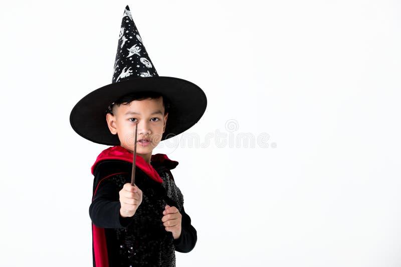 Νεαρός στο φόρεμα κοστουμιών μαγισσών που κρατά τη μαγικά ράβδο και το σημείο τ στοκ εικόνες με δικαίωμα ελεύθερης χρήσης