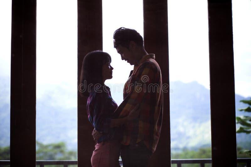 Νεαρότερος ασιάτης άνδρας και γυναίκα που αγκαλιάζονται με συναισθήματα αγάπης στοκ φωτογραφία