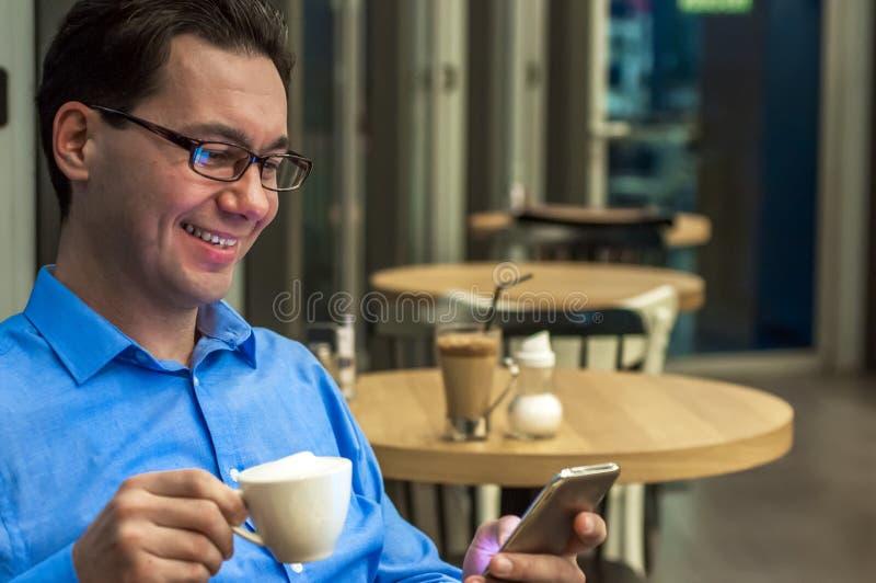 Νεαρών άνδρων στον καφέ Ευτυχής επιχειρηματίας που χαμογελά και που στο smartphone στον πίνακα στοκ εικόνες