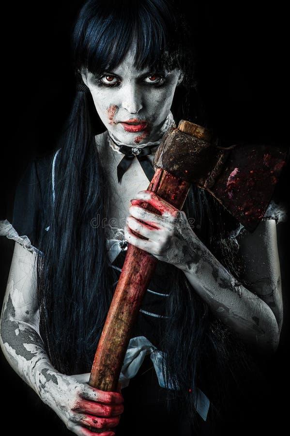 Νεκρό θηλυκό zombie με το αιματηρό τσεκούρι στοκ εικόνα