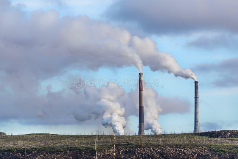 Νεκρό Tundra σε ένα υπόβαθρο των καπνίζοντας καπνοδόχων εργοστασίων στοκ εικόνα