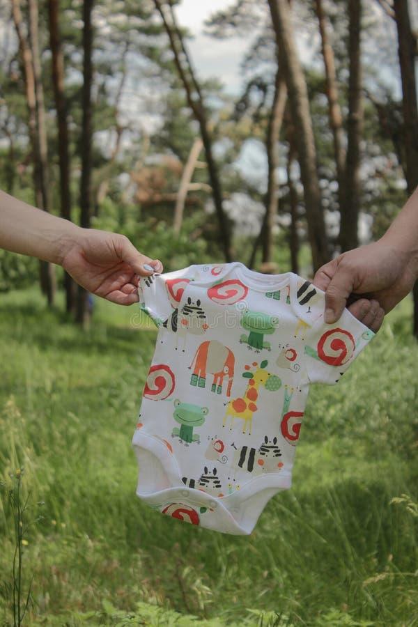 Νεογέννητα ενδύματα στα χέρια γονέων στοκ εικόνες