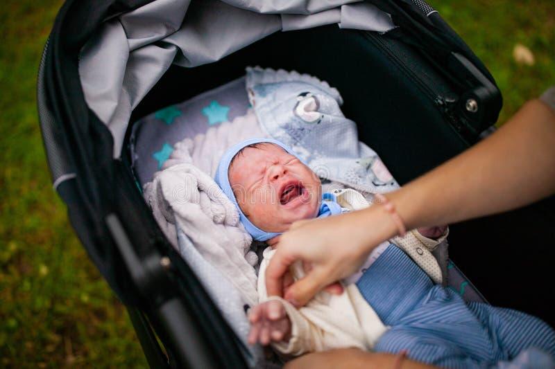 Νεογέννητη κραυγή μωρών που έχει το colic στενό επάνω πορτρέτο στοκ εικόνες