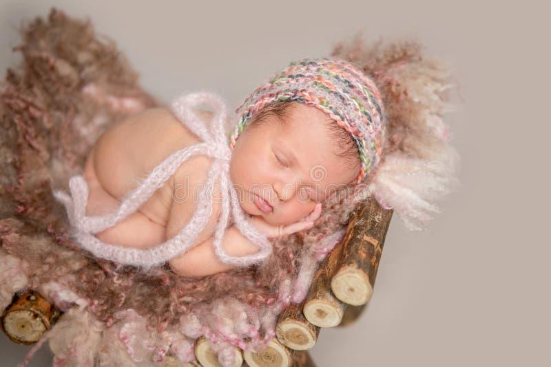 Νεογέννητος ύπνος κοριτσιών στο μικρό παχνί στοκ εικόνα με δικαίωμα ελεύθερης χρήσης
