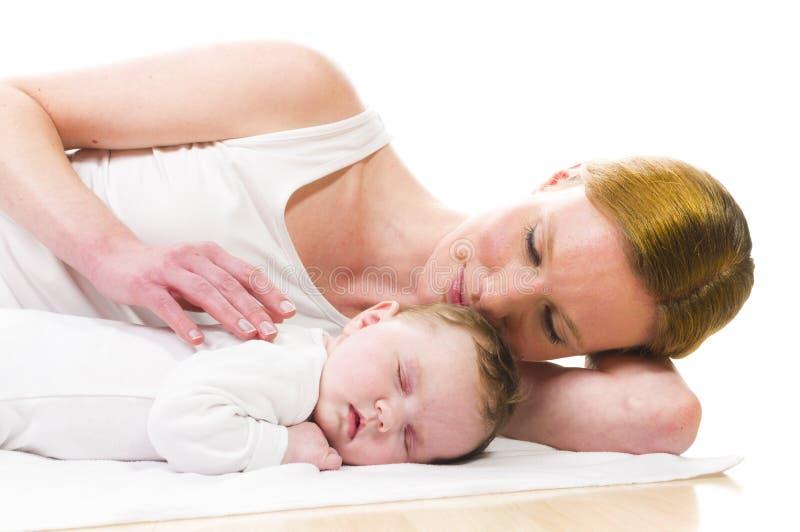 Νεογέννητος ύπνος μωρών με τη μητέρα στοκ φωτογραφία