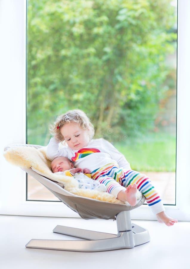 Νεογέννητο αγοράκι και η αδελφή του που χαλαρώνουν στην ταλάντευση στοκ φωτογραφία με δικαίωμα ελεύθερης χρήσης