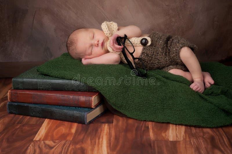 Νεογέννητο αγοράκι με τα γυαλιά ανάγνωσης στοκ εικόνες