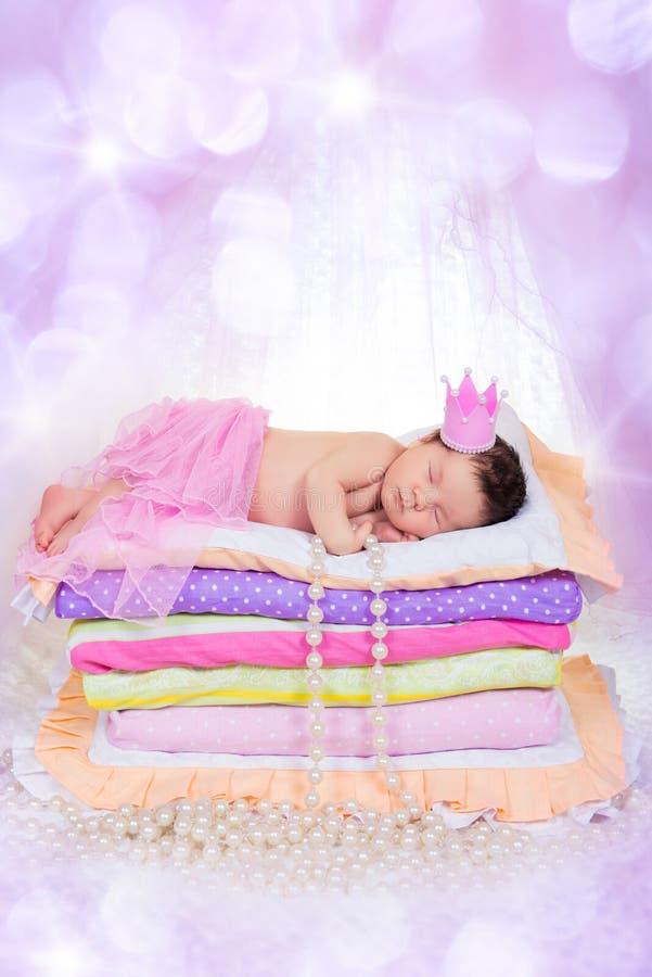 Νεογέννητο κοριτσάκι σε έναν ύπνο κορωνών στο κρεβάτι των στρωμάτων στοκ εικόνα