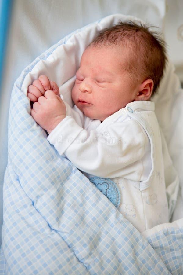 Νεογέννητο μωρό που βάζει στο παχνί στο προγενέθλιο νοσοκομείο στοκ φωτογραφία