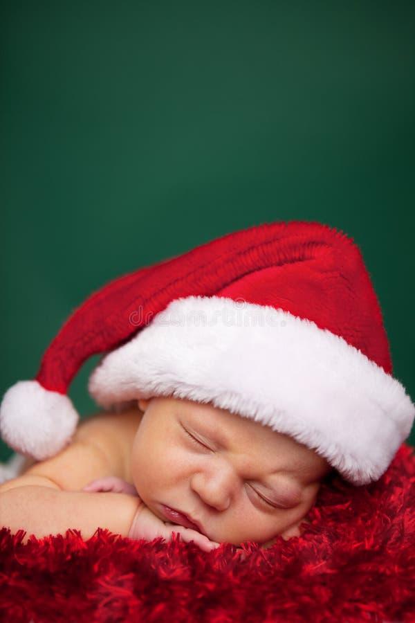 Νεογέννητο μωρό Χριστουγέννων που φορά το καπέλο και τον ύπνο Santa στοκ φωτογραφία με δικαίωμα ελεύθερης χρήσης