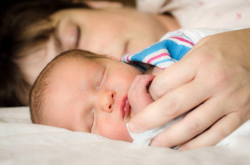 Νεογέννητο παιδί νηπίων που στηρίζεται δίπλα στη μητέρα μετά από την παράδοση στοκ εικόνες