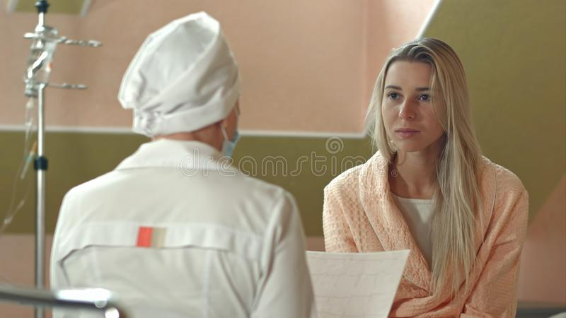 Νεολαίες γυναίκα στο νοσοκομειακό κρεβάτι που ακούει την πρόγνωση γιατρών στοκ εικόνες