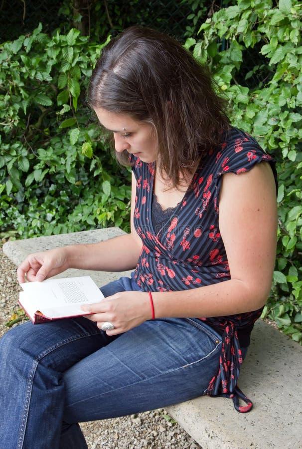 νεολαίες γυναικών ανάγνωσης πάγκων στοκ φωτογραφία