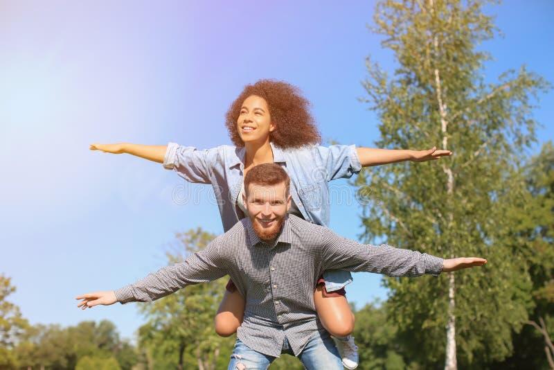 Νεολαίες που αγαπούν το διαφυλετικό ζεύγος που έχει τη διασκέδαση υπαίθρια την ημέρα άνοιξη στοκ φωτογραφία με δικαίωμα ελεύθερης χρήσης