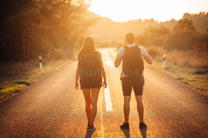 Νεολαίες που το τολμηρό ζεύγος που κάνει ωτοστόπ στο δρόμο Περιπέτεια της ζωής Τρόπος ζωής ταξιδιού Χαμηλό ταξίδι προϋπολογισμών  στοκ φωτογραφία