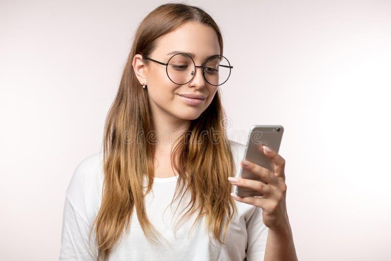 Νεολαίες που χαμογελούν την ξανθομάλλη γυναίκα που χρησιμοποιεί το τηλέφωνο που απομονώνεται στο άσπρο υπόβαθρο στοκ φωτογραφία