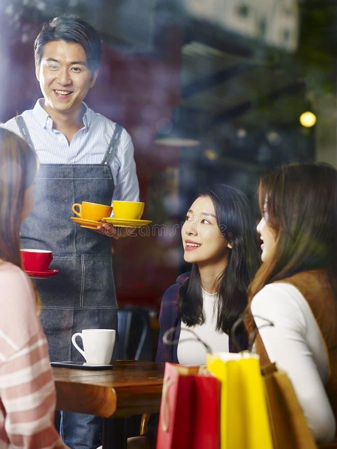Νεολαίες που χαμογελούν τον ασιατικό εξυπηρετώντας καφέ σερβιτόρων στους πελάτες στοκ φωτογραφία