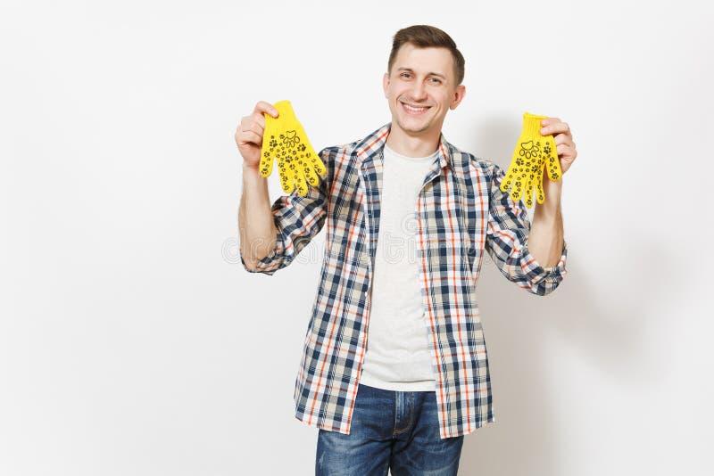 Νεολαίες που χαμογελούν το όμορφο άτομο στα περιστασιακά ενδύματα που κρατά τα κίτρινα γάντια οικοδόμησης με την τυπωμένη ύλη δια στοκ φωτογραφίες
