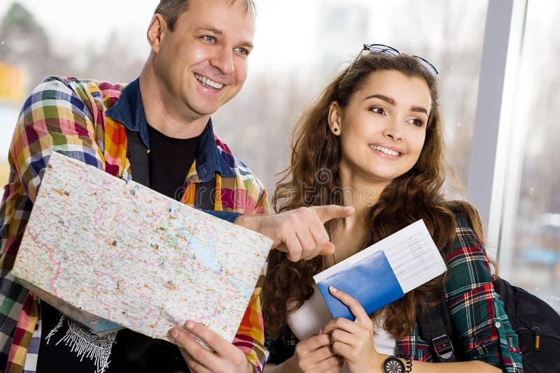 νεολαίες γυναικών ανδρών Κρατήστε έναν χάρτη και παρουσιάζει την κατεύθυνση Ευρωπαίοι Μαζευμένος σε μια οργανωμένη περιήγηση Κινη στοκ φωτογραφίες
