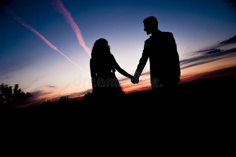 νεολαίες ηλιοβασιλέματος σκιαγραφιών ζευγών ανασκόπησης στοκ εικόνες