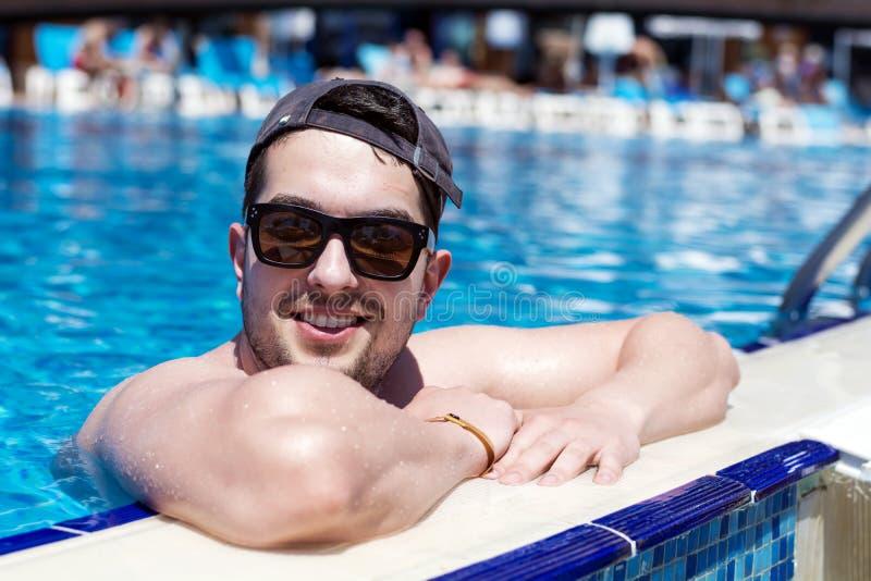 Νεολαίες που χαμογελούν τη μυϊκή χαλάρωση ατόμων στην πισίνα στοκ εικόνα με δικαίωμα ελεύθερης χρήσης