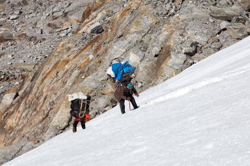 Νεπαλικοί αχθοφόροι βουνών που αναρριχούνται στον παγετώνα που φέρνει τις βαριές αποσκευές στοκ εικόνες