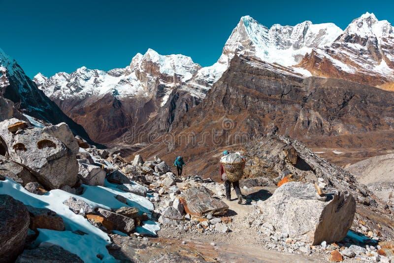 Νεπαλικός αχθοφόρος υψηλών βουνών και ευρωπαϊκή συνεδρίαση των οδοιπόρων για το μονοπάτι στοκ εικόνες με δικαίωμα ελεύθερης χρήσης